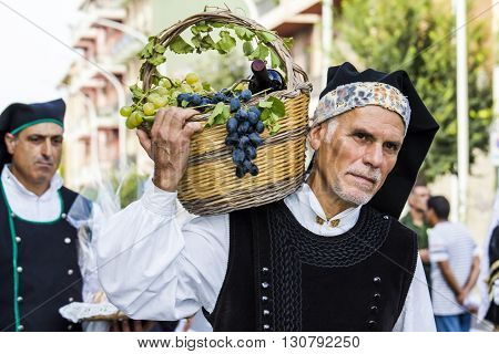 SELARGIUS, ITALY - 2015 September, 13: Former marriage Selargino - Sardinia - portrait of a man in Sardinian costume brings on his shoulder a basket of grapes