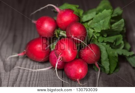 Ripe juicy red radishes with tops lying on a wooden table. Closeup with a small depth of field. dof