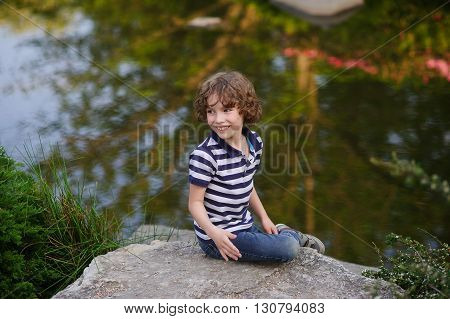 The boy sits on a background of a picturesque lake. The water reflects the green reeds, bushes and blue sky. The boy smiles
