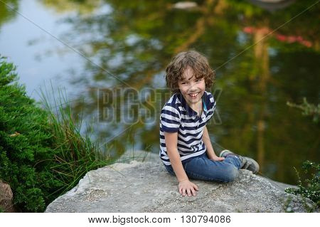 8-9 years boy sitting by the pond. Behind him, a quiet water surface. The pond reflects the sky and the green banks