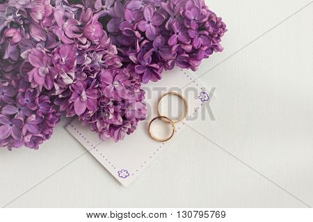 Wedding invitation with lilac flowers and rings. White vignette.