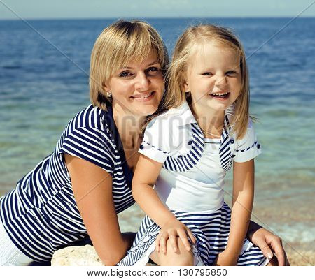 mother with daughter at sea cost together, happy real family lifestyle