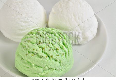 three scoops of white and green ice cream, vanilla, lemon, coconut, yogurt, buttermilk, pistachio, wood ruff, peppermint or kiwi flavor, on white plate, close up, horizontal, full frame