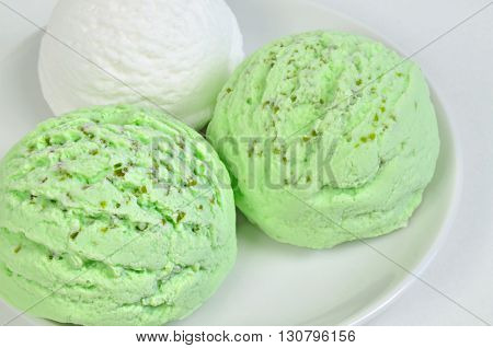 three scoops of green and white  ice cream, pistachio, woodruff, peppermint, kiwi, vanilla, lemon, coconut, yogurt or buttermilk  flavor,  on white plate, close up, horizontal, full frame