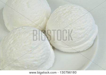 three scoops of white ice cream, vanilla, lemon, coconut, yogurt or buttermilk flavor, on white plate, close up, horizontal, full frame