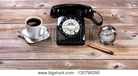 Vintage desktop with antique telephone pen clock and coffee on rustic wooden boards.
