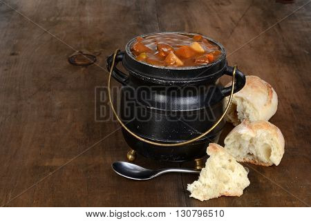 rustic beef stew with fresh bread and a spoon