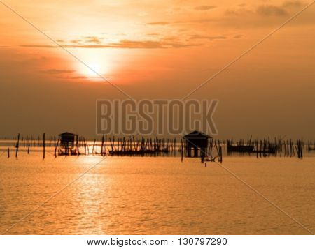 Blurred beautiful sunset above the sea in thailand. Silhouette of fish farms at sunset.