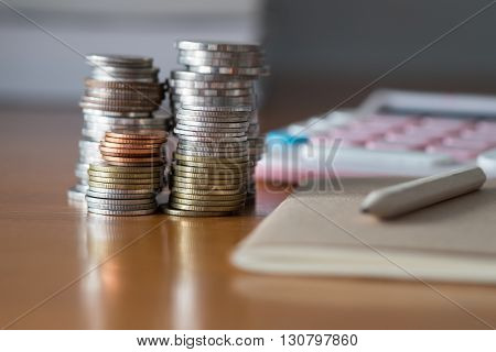 Pencil, notebook, coins and calculator on wooden table.