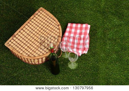 top view picnic basket with wine on grass