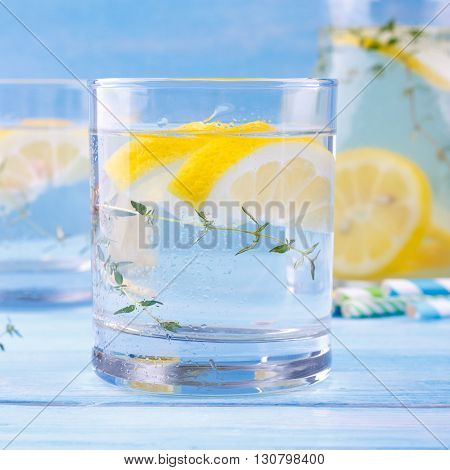 Closeup of beverage with lemon and thyme, on blue wooden background
