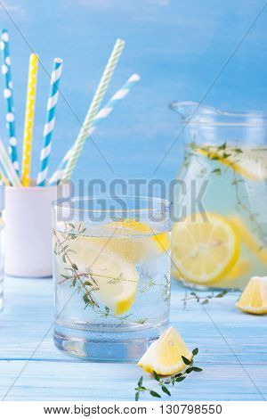 Cool beverage with lemon and thyme, on blue wooden background