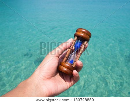 lady hand holding hourglass sandglass against with green blue sea water surface in background. Time to vacation holiday summer concept. Slow life concept.