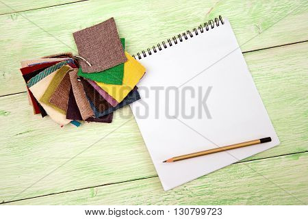 notebook and colored fabric on wooden green background