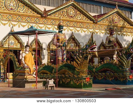 Stautes of soldiers and and dragons stand in the courtyard of a colorful Burmese Buddhist temple