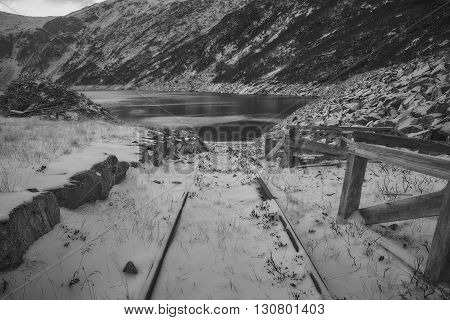 A disused rail track covered in snow at the bank of Norwegian fjord. During warmer months it is now used to launch boats in the fjord.