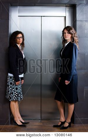 Two businesswomen waiting for the elvator at office lobby.