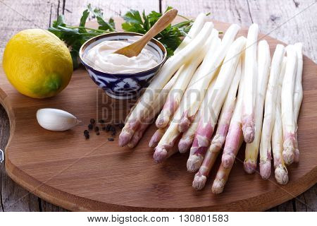 Peeled asparagus and ingredients for a sauce on wooden board