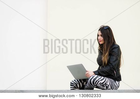 Portrait of a pretty woman sitting outdoors with laptop