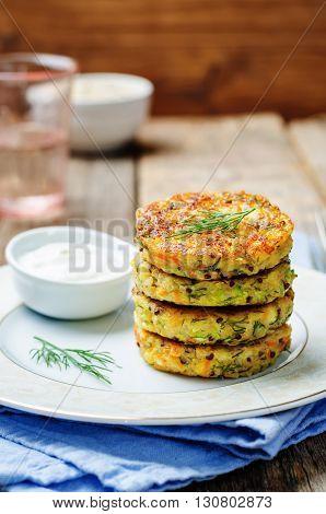 Quinoa Zucchini feta dill fritters on dark wooden background.