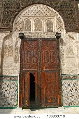 Elaborate door of carved cedar at the Medersa Bou Inania an ancient madrasa in the Fes el Bali medina in Fez Morocco