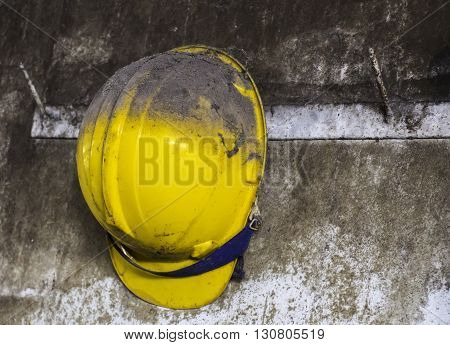 yellow construction helmet hanging on hat rack.