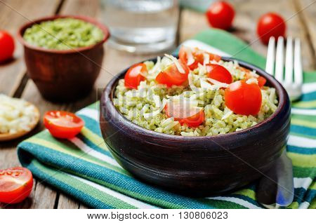 Pesto rice with tomatoes and cheese on a dark wood background.