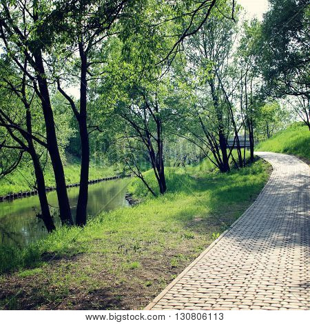 Walking path near the river. Morning run route. Paved walking path along the river. Aged photo. Early spring. Outdoors pavement path along a river. Park in a sunny day. Green trees near river.