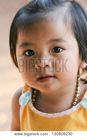 UMPHANG, THAILAND, DECEMBER 12, 2006 : Thai little girl portrait outside her mother's shop in the Umphang province, Thailand