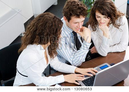 Happy young business people sitting by table at office, working together on laptop computer, smiling. High-angle view.
