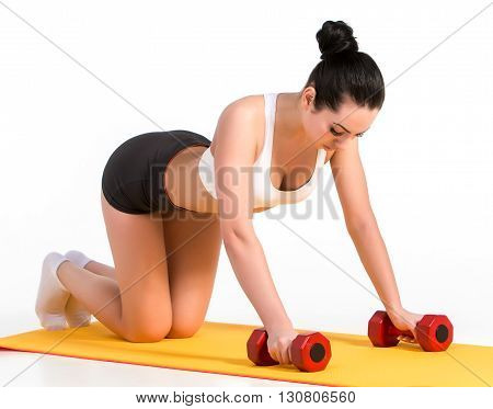 Strong young woman doing push ups exercise with dumbbells. Fitness model doing intense training on an yellow mat.