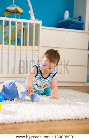 Sweet baby boy ( 1 year old ) sitting on floor at home and playing with soft toys at children's room.
