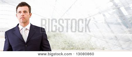 Mid adult businessman standing in front of windows inside officebuilding, looking away. Business banner.
