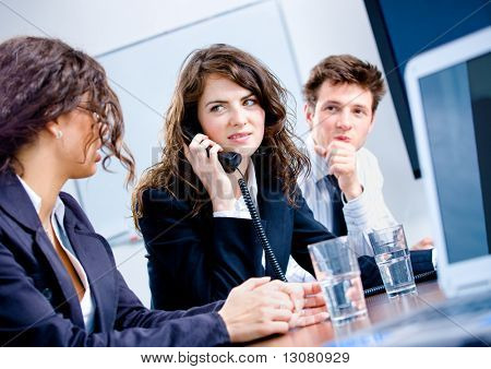 Young business people having meeting at office, businesswoman calling on phone.