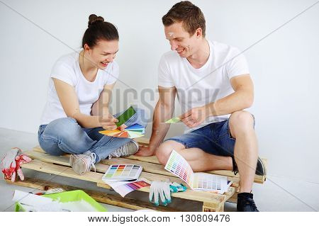 Cheerful young couple sitting on a wooden pallet on the white walls. They choose the catalog for paint repairs