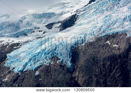 The blue ice of a glacier clings to a rocky mountain side.