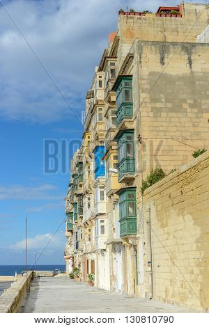 House with balconys on Malta at seaside in summer