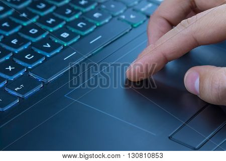 Man Using Touchpad On Notebook Keyboard With His Finger
