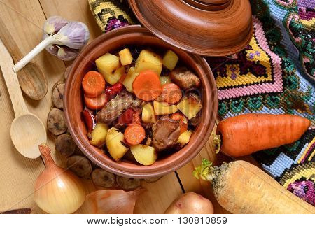 Beef stew with vegetables in a pot, top view