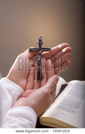 Christian believer holding old cross in hand.