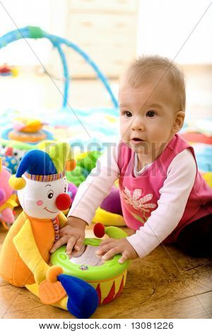 Baby girl (9 months) playing with soft toys at home. Toys are property released.