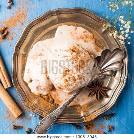 Scoop of homemade ice cream with cinnamon, apple syrup and spices on metal plate on blue wooden background. Summer food concept. Top view.