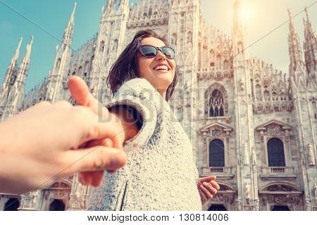 Smiling woman hold his boyfriend hand on Duomo di Milano background