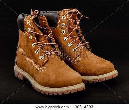 Pair of Brown lady's boots with shoelace on black background. Toes turned right on diagonal