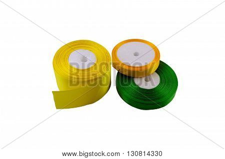 macro yellow orange and green tapes on reels all for sewing and needlework isolate on a white background