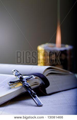 Cruz antigua y la Santa Biblia, poniendo sobre la mesa delante de una vela de iluminación.