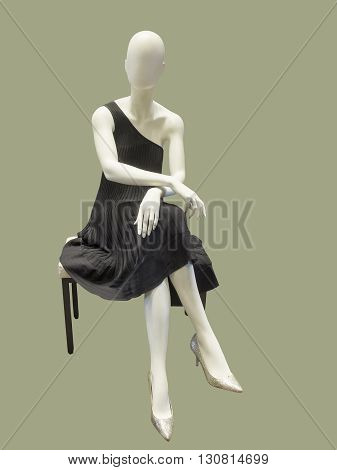 Sitting female mannequin dressed in black evening gown against green background. No brand names or copyright objects.