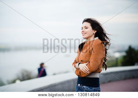 Beautiful outdoors portrait of a woman in leather coat