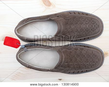Brown pair of suede men's summer shoes with red price tag on wooden background