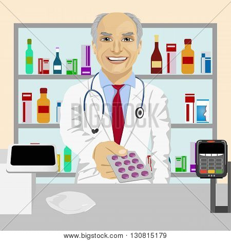 Senior male pharmacist giving pills in a blister pack standing in a drugstore in front of medications on showcase